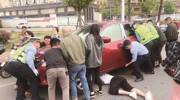 男子被压车下 警民合力抬车