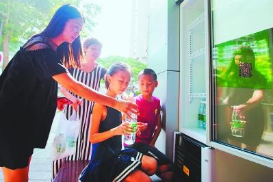 """两位放暑假的孩子,在妈妈的引领下用自己的零花钱买来矿泉水为""""爱心冰箱""""补充能量。"""