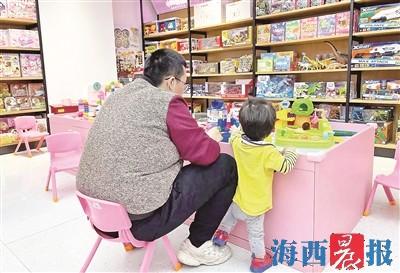 加州商业广场一玩具租赁体验店内,家长带着孩子玩耍。