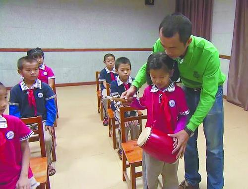 ■詹江贺引导山区的孩子和城里的孩子同上一堂音乐课。