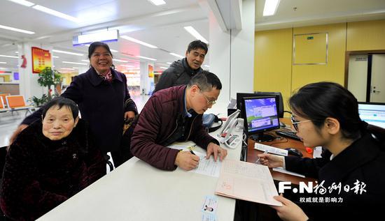 从美国纽约回乡的郑先生昨日与家人在市民服务中心办理房产手续。