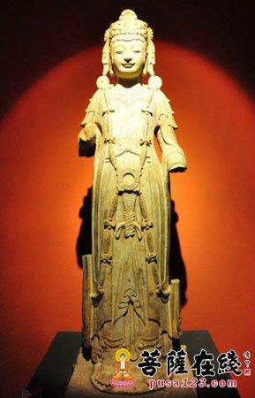 北魏晚期至东魏的圆雕菩萨立像,顶梳发髻,戴冠,上身着右袒偏衫,前襟束于腰带呈现三波垂悬纹