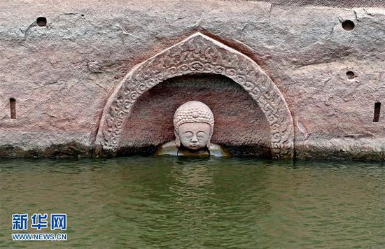 露出水面的佛头遗迹(记者 万象 摄)