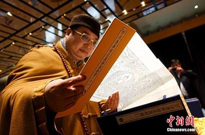 延藏法师翻阅《清敕修大藏经》。(中新网  摄影:杜洋)