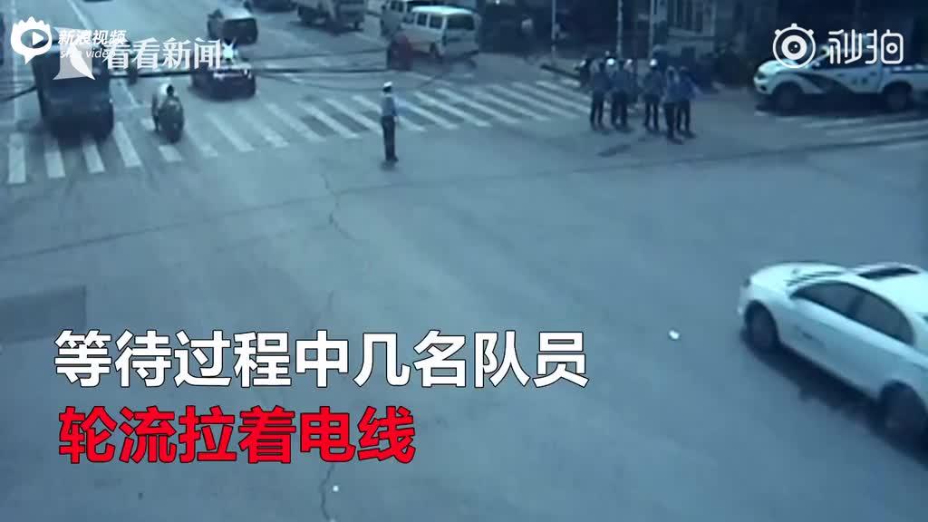 空中电缆掉落 警辅人员双手托举避免路面拥堵