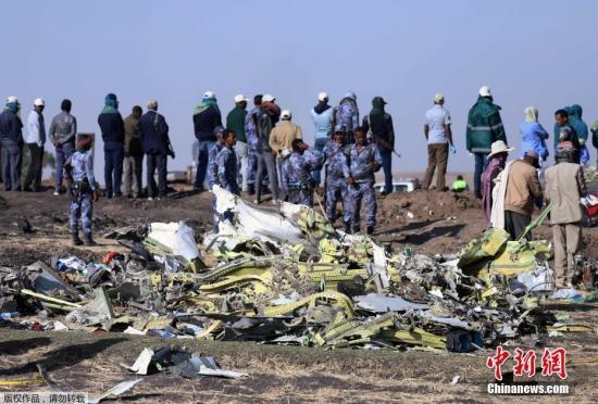 当地时间3月11日,在埃塞俄比亚首都亚的斯亚贝巴附近,救援人员在坠机现场清理飞机残骸。