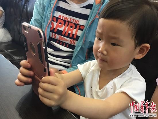 5月14日,天津一家餐厅,一名3岁儿童在等餐期间,用家长的手机聚精会神玩儿游戏。