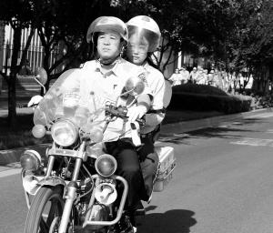 沈队长驾驶摩托车送考生到六中 本报记者 张海强 摄
