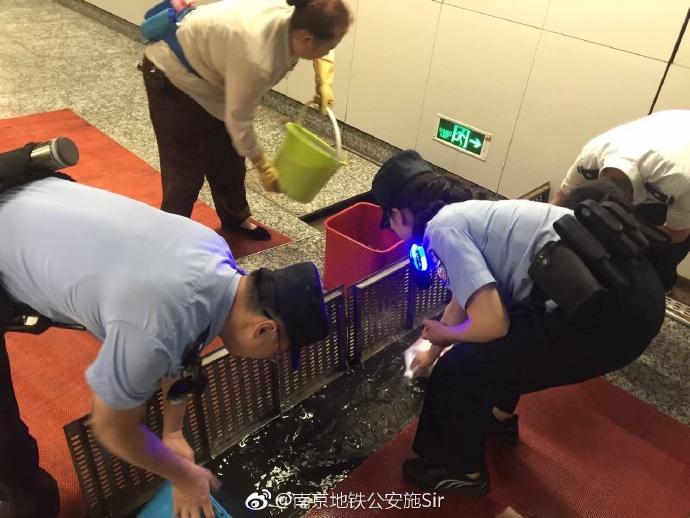 雨水倒灌致地铁站积水严重 民警用水桶舀除积水