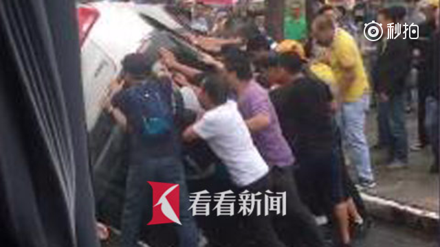 高架下轿车侧翻妇女被压 众人援手抬车救人