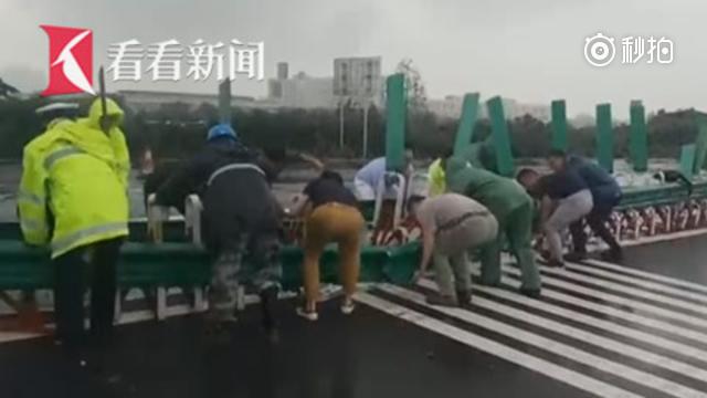 暖心 高速中央护栏被撞倒 数十位路过车主冒雨扶起
