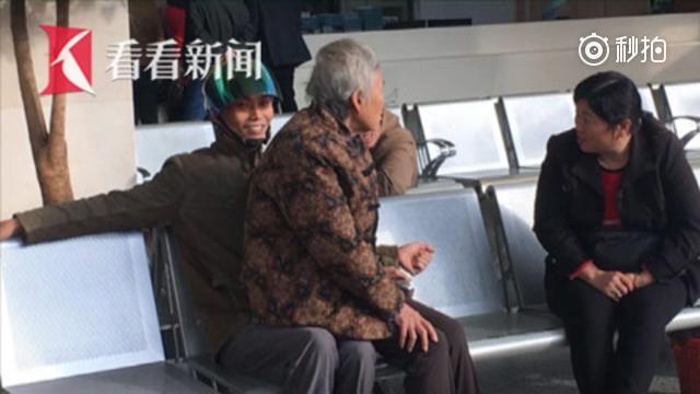 担心母亲直接坐到椅子上受凉 中年男子抱母为其取暖