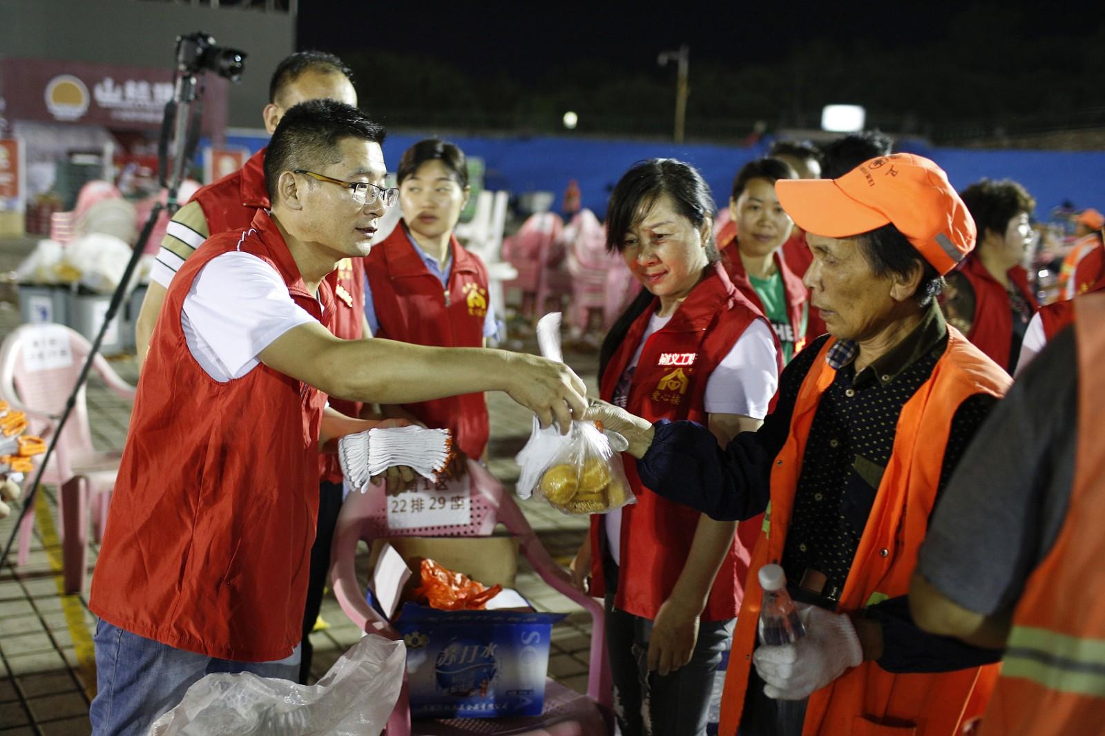2018年6月14日凌晨,在江苏省盱眙县都梁公园龙虾广场,爱心志愿者向环卫工赠送手套和食品。