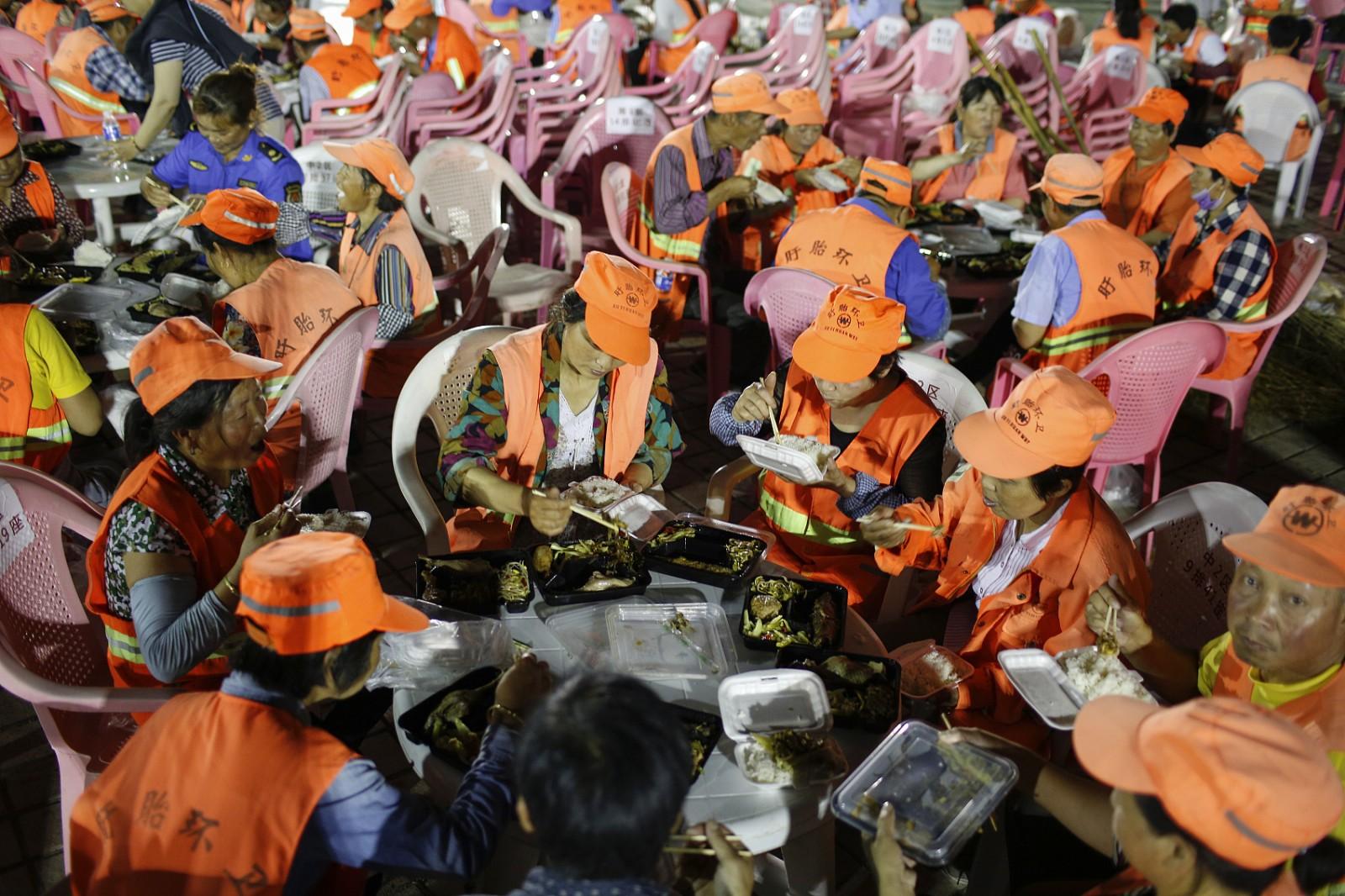 2018年6月14日凌晨,在江苏省盱眙县都梁公园龙虾广场,环卫工人在吃夜餐。