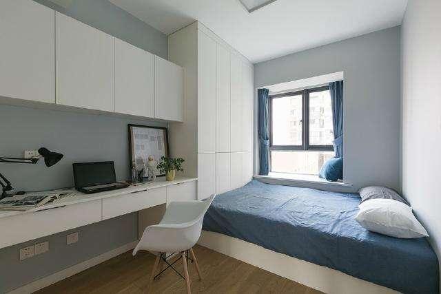 次卧,带着飘窗,灰色的墙壁,有一个办公桌.