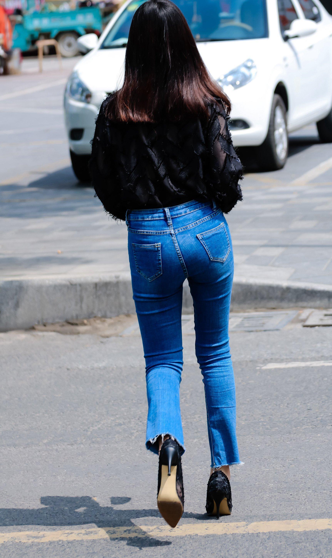 紧身牛仔裤_街拍:紧身牛仔裤搭配黑色薄纱长袖上衣,这样的牛仔裤简便又好看