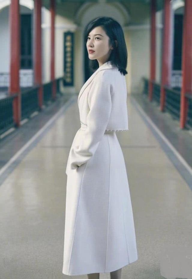 橘红色头�_姗身穿一件白色的长裙,加上一件同色系的外套,裙摆有两个口袋,可以插
