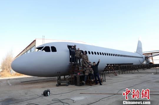 """辽宁铁岭6位农民历时一年制成""""空客A320"""",完工前夕在飞机前合影。"""