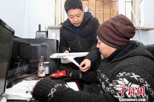 """辽宁铁岭6位农民历时一年制成""""空客A320"""",主创者朱跃与设计人员交流。 本文图片均为 杨也迅 摄"""