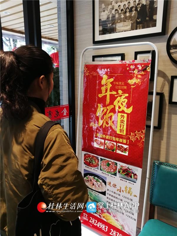 """市民在解放西路一家餐馆看年夜饭""""外卖打包""""的宣传展板。"""