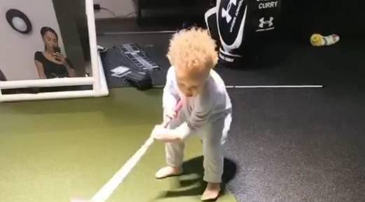 库里在自家的高尔夫模拟器前开始教儿子卡侬打球,在库里的示范下