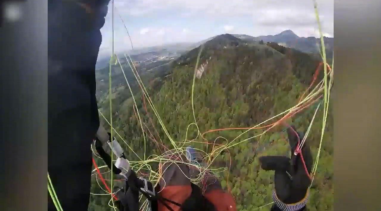 高空惊魂一刻 法国男子玩滑翔伞被绳缠住