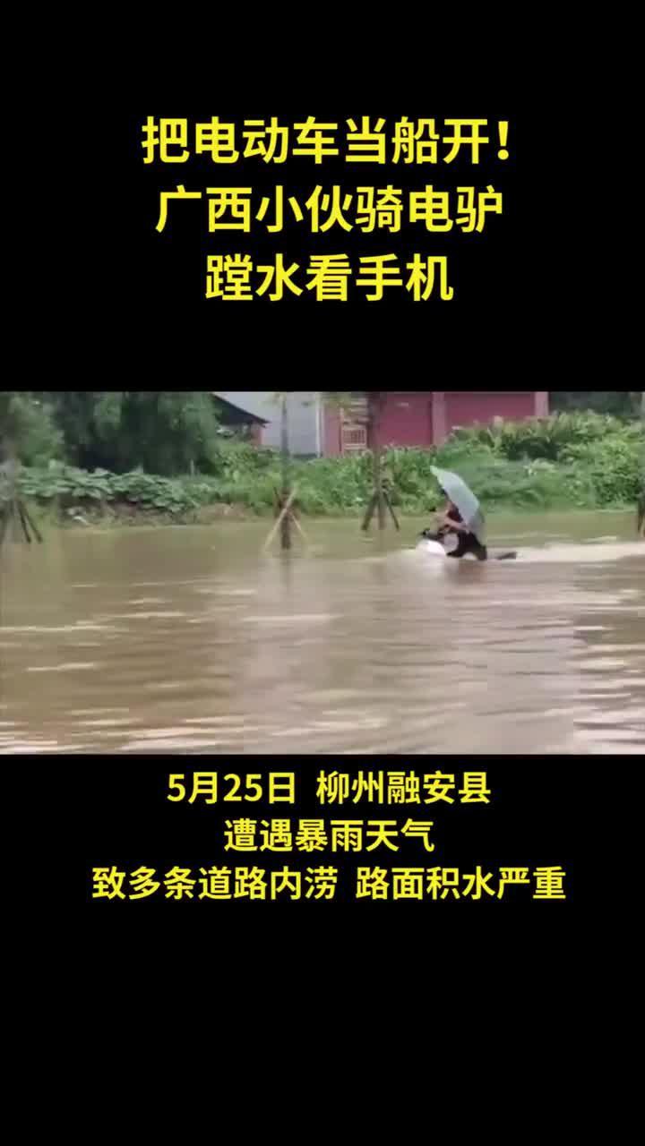 厉害了!小伙撑伞骑电驴蹚水还玩手机