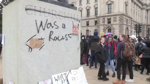 英国伦敦抗议活动现场一名男子踢开并撕下了反种族主义示威者在温斯顿·丘吉尔雕像上放置的抗议标语