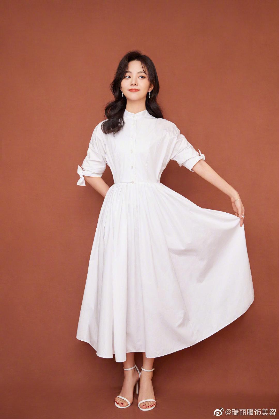 身着白色长裙搭配戴比尔斯 (DE BEERS) Horizon密镶戒指、Dewdrop