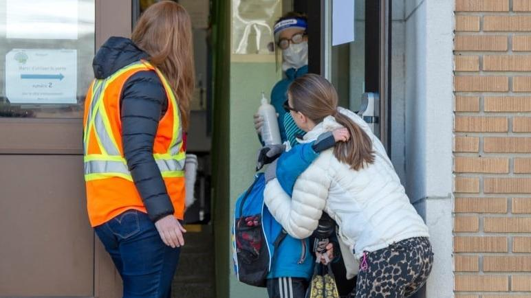 △5月11日,魁北克省的一位媽媽把孩子送到一所學校(圖片來自加拿大廣播公司)