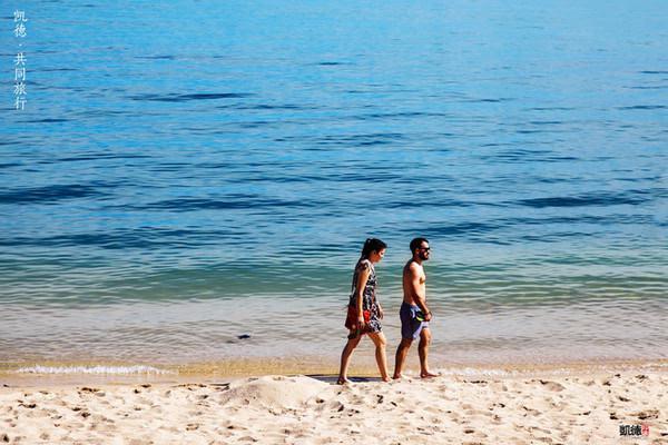 在沙滩上慢慢走着的一对度假夫妻