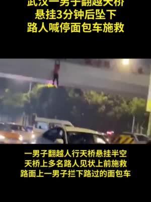 武汉一男子翻越天桥悬挂后坠下 路人喊停面包车接住