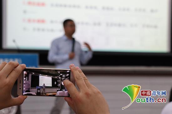 活动现场,南开大学学生用手机拍摄记录讲义。中国青年网通讯员杨至摄