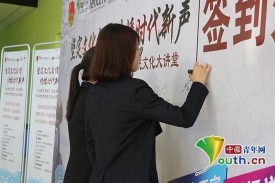 """活动开始前,学生们在""""坚定文化自信传播时代新声""""签到板前签到。中国青年网通讯员 杨至摄"""