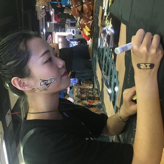 参与活动的粉丝认认真真地在队旗上写下名字