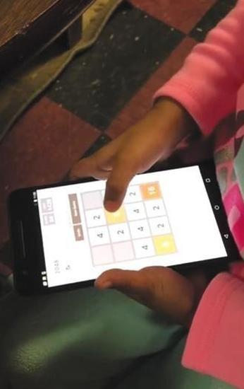 """一名儿童正在安卓系统的智能手机上玩""""2048""""游戏,进行iCare软件的实验"""