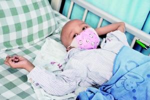 5岁女童患肉瘤来广州治病 疼痛时拿纸巾擦擦眼泪