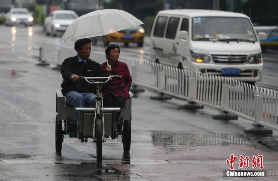 资料图:民众在雨中出行。中新社记者 贾天勇 摄