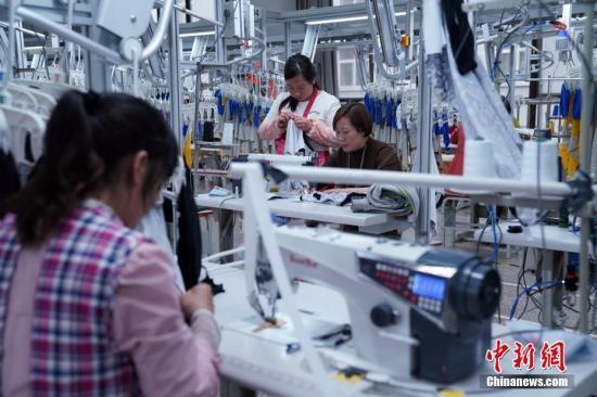 资料图:工人在勉县制衣厂生产线工作。 毛建军 摄