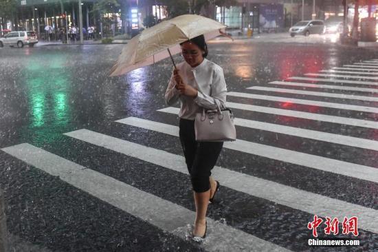 5月7日,广州街头,一名女子撑伞行走在雨中。 中新社记者 陈骥旻 摄