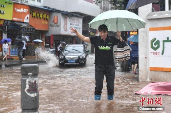 资料图:6月8日,广州天河区员村二横路,一名女子涉水出行。 中新社记者 陈骥旻 摄