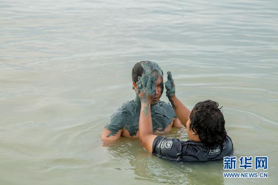 游客在海水中享受泥浆浴