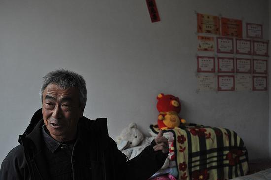 2月3日,农历腊月二十九。李玉宝特意把记者拉到儿子的房间,墙上贴满孙女的奖状,这是他的骄傲。 新京报记者 吴江 摄