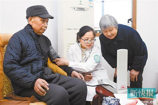 ■医护人员在市民家中提供护理服务(资料图片)。   新华社发