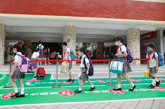 广州市天河区华康小学学生排队测量体温。