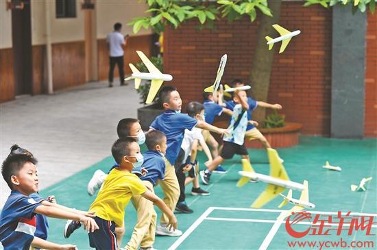 19日,广州暑期校内托管的第一天,小北路小学天香街校区,学生们在操场放飞飞机模型 羊城晚报全媒体记者 林桂炎 摄