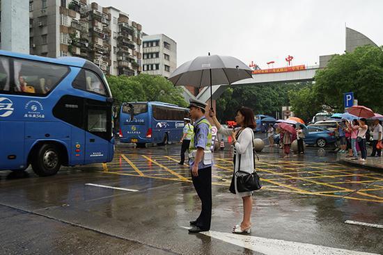 一名女性家长为值勤交警打伞 江门交警 供图
