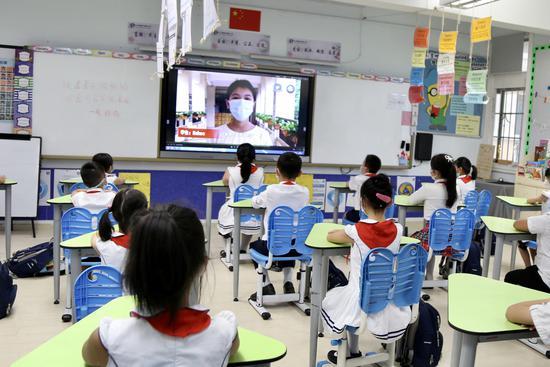白云区中大附属外国语小学高年级学生给低年级学生加油打气。