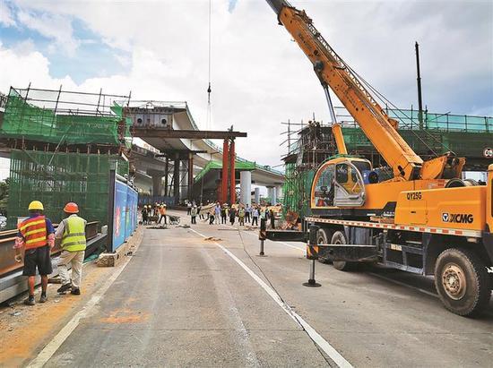 ◀救援的大型吊车对坍塌的桥梁支架、变形的钢筋等障碍进行清除。