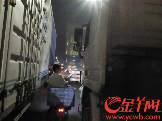 外卖小哥穿梭在货车与货车狭小的缝隙里给司机送餐